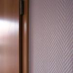 Tür und Wand mit weißer Tapete